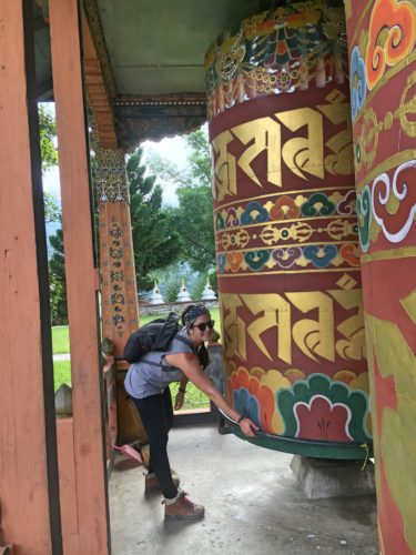 me spinning a large prayer wheel in punakha