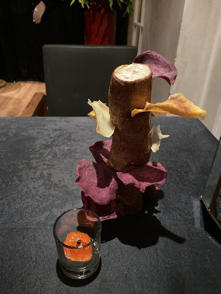 A cassava with chips stuck in the side and a candle that is dip