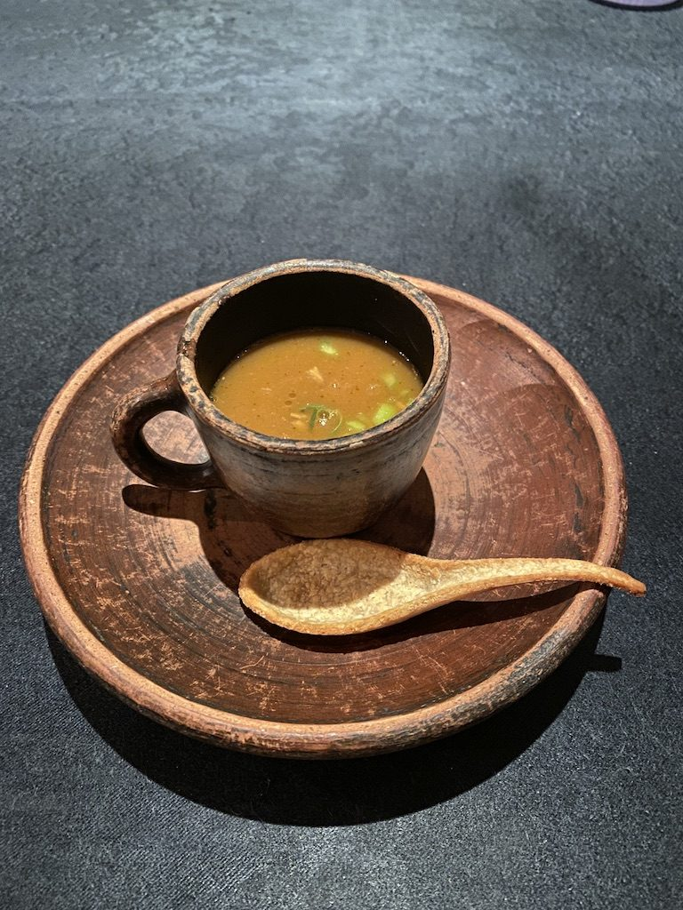 Beef soup in a clay pot with a cracker spoon at Namaaz Dining